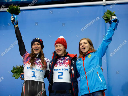 From left to right, silver medalist Noelle Pikus-Pace of the United States, gold medalist, Elizabeth Yarnold of Great Britain and bronze medalist Elena Nikitina of Russia pose during the flower ceremony after the women's skeleton competition at the 2014 Winter Olympics, in Krasnaya Polyana, Russia