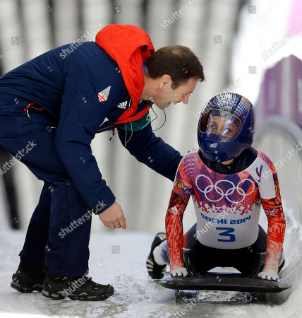 Shelley Rudman of Great Britain is greeted by her coach after her second run during the women's skeleton competition at the 2014 Winter Olympics, in Krasnaya Polyana, Russia