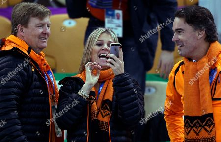 Dutch Queen Maxima looks into her phone, with King Wilem-Alexander, left, and KLM CEO and IOC member Camiel Eurlings by her side during the women's 3,000-meter speedskating race at the Adler Arena Skating Center during the 2014 Winter Olympics, in Sochi, Russia