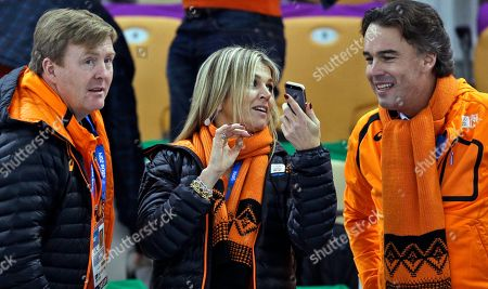 Dutch King Wilem-Alexander, left, watches the race as Queen Maxima shows her phone to KLM CEO and IOC member Camiel Eurlings during the women's 3,000-meter speedskating race at the Adler Arena Skating Center during the 2014 Winter Olympics, in Sochi, Russia