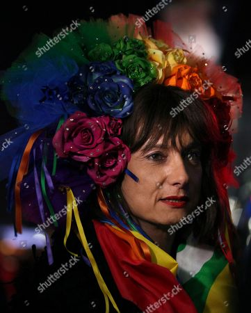 """Vladimir Luxuria, a former Communist lawmaker in the Italian parliament and prominent crusader for transgender rights, walks in Olympic Park at the 2014 Winter Olympics, in Sochi, Russia. Luxuria said she was detained by police at the Olympics after being stopped while carrying a rainbow flag that read in Russian: """"Gay is OK."""" Police on Monday denied this happened"""