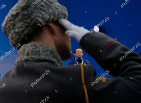 Akira Kano A Russian honor guard soldier salutes as Akira Kano of Japan, winner of the men's downhill sitting skiing event, listens to the Japanese national anthem during medal ceremony at the 2014 Winter Paralympic, in Krasnaya Polyana, Russia