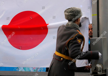 A Russian honor guard soldier lifts national Japan flag in honor Akira Kano of Japan, winner of the men's downhill sitting skiing event, during medal ceremony at the 2014 Winter Paralympic, in Krasnaya Polyana, Russia