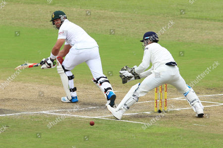 South Africa's batsman Jacques Kallis, left, plays a side shot as India's captain Mahendra Singh Dhoni, right, on the forth day of their cricket test match at Kingsmead stadium in Durban, South Africa