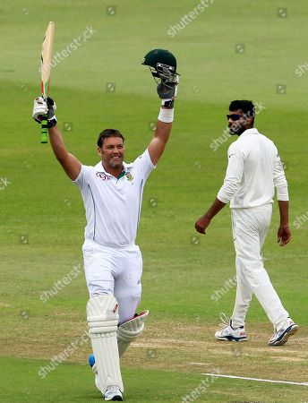 South Africa's batsman Jacques Kallis, left, celebrates his century as India's bowler Ravindra Jadeja, right, watches on the forth day of their cricket test match against India at Kingsmead stadium in Durban, South Africa