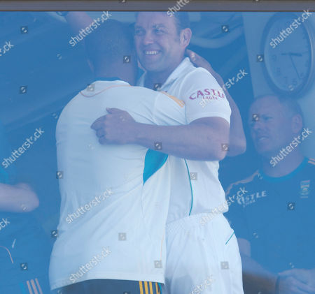 South Africa's Jacques Kallis, right, embraces teammate Vernon Philander in the pavilion after retiring from Test cricket at the end of their fifth and final day of their cricket test match against India at Kingsmead stadium, Durban, South Africa, . South Africa beat India by 10 wickets