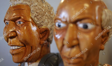 Stock Image of A wood carving of former South African president Nelson Mandela by South African artist Richard Chauke, left, next to his counterpart, former South African president F. W. de Klerk, is displayed at a art exhibition in his honor in Cape Town, South Africa, . Twenty two artist paid tribute to Nelson Mandela creating art accessible to a wide audience