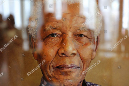 A reflection is seen on a painting of former South African president Nelson Mandela by British artist Richard Stone, at a art exhibition in his honor at Cape Town, South Africa, . Twenty two artist paid tribute to Nelson Mandela, creating art accessible to a wide audience