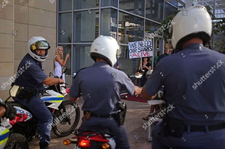 Police officers on motorbike stay on alert as protesters stage a rally againsst the Western Australian Government's catch and kill shark policy adopted by Premier Colin Barnett in Cape Town, South Africa, . The West Australian government's new catch-and-kill policy was announced in December, following seven fatal attacks off the Western Australian coast in three years. Premier Colin Barnett has defended the policy, arguing public safety is at risk
