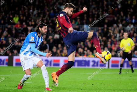 Gerard Pique, Sergio Sanchez FC Barcelona's Gerard Pique, right, duels for the ball with Malaga's Sergio Sanchez during a Spanish La Liga soccer match at the Camp Nou stadium in Barcelona, Spain