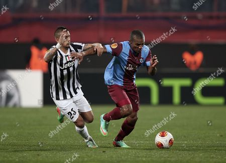 Arturo Vidal, Florent Malouda Trabzonspor's Florent Malouda, right, and Arturo Vidal of Juventus fight for the ball during their Europa League Round of 32 soccer match at Avni Aker Stadium in Trabzon, Turkey