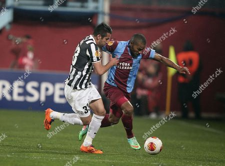 Mauricio Isla, Florent Malouda Trabzonspor's Florent Malouda, right, and Mauricio Isla of Juventus fight for the ball during their Europa League Round of 32 soccer match at Avni Aker Stadium in Trabzon, Turkey