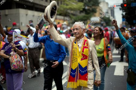Pedro Pablo Rivero, 81, lifts his hat during a rally by elderly people in Caracas, Venezuela, . The march was organized by the government in the name of peace, and ended at Miraflores presidential palace where the seniors met with Venezuela's President Nicolas Maduro