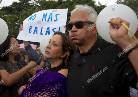 """Venezuelan Actress Elba Escobar, center, and her husband Francisco Oilvares, right, protest against the murder of Monica Spear and her ex-husband Henry Thomas Berry in Caracas, Venezuela, . The sign in the background reads in Spanish """"No More Bullets."""" Venezuelan authorities say the former Miss Venezuela and her ex-husband were shot and killed resisting a robbery after their car broke down late Monday, Jan. 6, 2014 near Puerto Cabello, Venezuela's main port"""