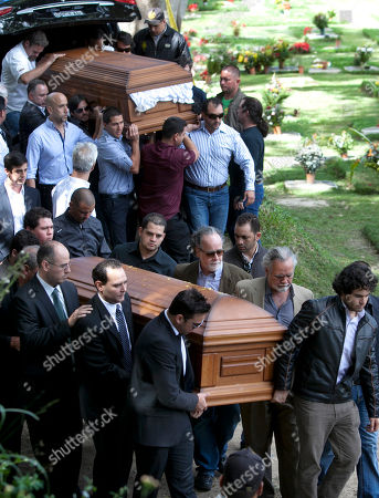 Relatives and friends carry the remains of Monica Spear, below, and of her ex-husband Thomas Henry Berry, top, during their funeral at the East Cemetery in Caracas, Venezuela, . Robbers killed actress Spear, 29, and her former husband Berry, 39, late Monday night on an isolated stretch of highway while the couple was returning to the capital by car with their 5-year-old daughter from a vacation