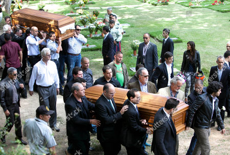 Relatives and friends carry the remains of Monica Spear, right, and of her ex-husband Thomas Henry Berry, top left, during their funeral at the East Cemetery in Caracas, Venezuela, . Robbers killed actress Spear, 29, and her former husband Berry, 39, late Monday night on an isolated stretch of highway while the couple was returning to the capital by car with their 5-year-old daughter from a vacation