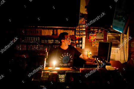 Stock Picture of David Franco David Franco, from Colombia, works by candlelight at a convenience store that lost electricity one hour beforehand Buenos Aires, Argentina, . Power outages continue in Argentina's capital, where electricity usage is setting new records amid 100-degree (37.8 Celsius) temperatures in the Southern Hemisphere summer