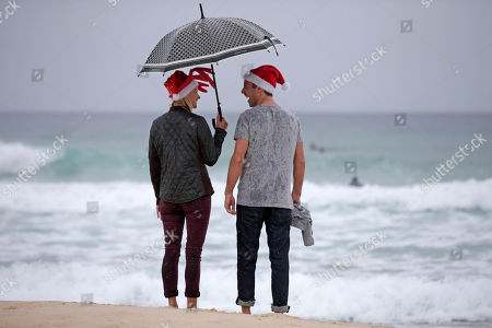 Scott Relf, right, and his British girlfriend Lauren Harris laugh as they stand in the rain on Bondi Beach to celebrate Christmas Day in Sydney