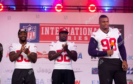 San Francisco 49ers' injured British defensive end Lawrence Okoye, right, is interviewed on stage flanked by linebackers NaVorro Bowman, left, and Patrick Willis, center, during an NFL fan rally in Trafalgar Square, London, . The San Francisco 49ers are due to play the the Jacksonville Jaguars at Wembley stadium in London on Sunday, Oct. 27 in a regular season NFL game