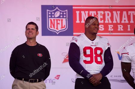 San Francisco 49ers head coach Jim Harbaugh, left, and injured British defensive end Lawrence Okoye appear on stage during an NFL fan rally in Trafalgar Square, London, . The San Francisco 49ers are due to play the the Jacksonville Jaguars at Wembley stadium in London on Sunday, Oct. 27 in a regular season NFL game