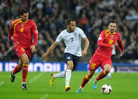 England's Andros Townsend, centre, runs with the ball watched by Montenegro's Nikola Drincic, right and teammate Milan Jovanovic during the World Cup Group H qualification soccer match between England and Montenegro at Wembley stadium in London