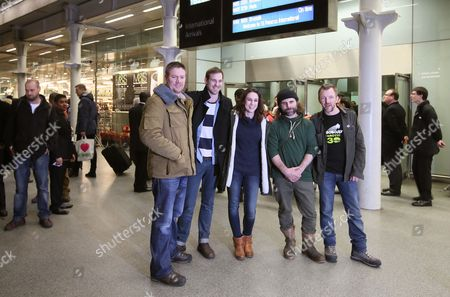 The five British Greenpeace activists, crew members and video journalist who were part of the 30 Greenpeace activists arrested in the Russian Arctic, pose for the media as they arrive back in London, from left: Anthony Perrett, activist, Kieron Bryan, freelance videographer, Alexandra Harris, activist, Ian Roger, crew member and, Phill Ball, activist, . Russian investigators have dropped charges against all but one of the 30 crew of a Greenpeace ship, who were accused of hooliganism following a protest outside a Russian oil rig in the Arctic, the group said Wednesday. The criminal charges against the crew were closed under an amnesty that was passed by the parliament earlier this month, seen by many as an attempt by the Kremlin to dampen the criticism of Russia's human rights record before the Winter Olympics in Sochi in February
