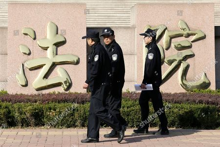 """Policemen walk past Chinese characters reading """"courthouse,"""" which is part of the sign for Shandong Province Supreme People's Court in Jinan, in eastern China's Shandong province, . The court will hold a hearing on Friday to rule on disgraced politician Bo Xilai's appeal against the guilty verdict and life imprisonment he was handed last month. Bo was found guilty of embezzlement, bribery and abuse of power by a lower court last month and sentenced to life in prison. He has denied the charges"""