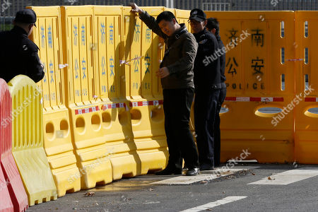 Policemen, in plainclothes and uniforms, arrange road dividers working as fences of a cordoned off area for journalists outside a gate of Shandong Province Supreme People's Court in Jinan, in eastern China's Shandong province, . The court will hold a hearing on Friday to rule on disgraced politician Bo Xilai's appeal against the guilty verdict and life imprisonment he was handed last month. Bo was found guilty of embezzlement, bribery and abuse of power by a lower court last month and sentenced to life in prison. He has denied the charges