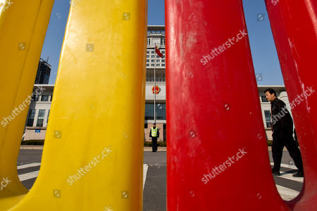 Seen through the holes of red and yellow road dividers used as fences of a cordoned off area for journalists, a plainclothes policeman, right, patrols while a traffic policeman, center, stands outside a gate of Shandong Province Supreme People's Court in Jinan, in eastern China's Shandong province, . The court will hold a hearing on Friday to rule on disgraced politician Bo Xilai's appeal against the guilty verdict and life imprisonment he was handed last month. Bo was found guilty of embezzlement, bribery and abuse of power by a lower court last month and sentenced to life in prison. He has denied the charges