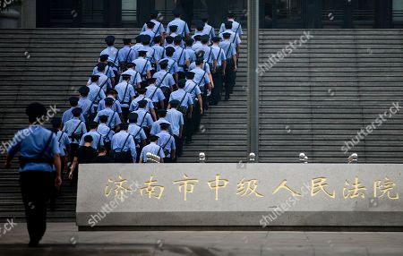 Chinese police officers march into the Jinan Intermediate People's Court to prepare for the arrival of fallen politician Bo Xilai in Jinan in eastern China's Shandong province on . The Chinese court was expected to hand down a guilty verdict Sunday for corruption charges against Bo in one of the country's most lurid political scandals in decades