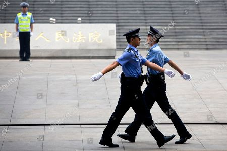 Chinese police officers march as they change shifts outside the Jinan Intermediate People's Court in Jinan in eastern China's Shandong province on . The Chinese court was expected to hand down a guilty verdict Sunday for corruption charges against fallen politician Bo Xilai in one of the country's most lurid political scandals in decades
