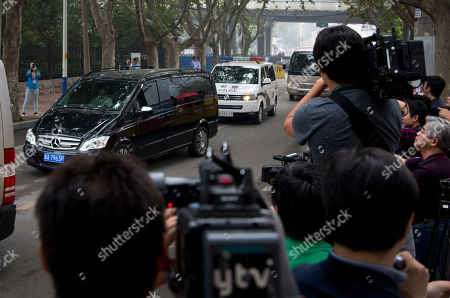 Journalists film a van, left, believed to be carrying fallen politician Bo Xilai, escorted by a convoy of vehicles as it arrives at the Jinan Intermediate People's Court in Jinan in eastern China's Shandong province on . The Chinese court was expected to hand down a guilty verdict Sunday for corruption charges against Bo in one of the country's most lurid political scandals in decades