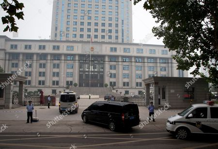 A van, center believed to be carrying fallen politician Bo Xilai is escorted by a convoy of vehicles as it arrives at the Jinan Intermediate People's Court in Jinan in eastern China's Shandong province on . The Chinese court was expected to hand down a guilty verdict Sunday for corruption charges against Bo in one of the country's most lurid political scandals in decades