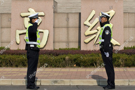 """Two traffic policemen salute each other outside Shandong Provincial Higher People's Court where ousted politician Bo Xilai is temporarily held for a ruling to his appeal against his conviction in Jinan, in eastern China's Shandong province, . Chinese characters in the back reads """"higher class"""" as part of a sign for the court"""