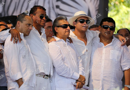 From left to right, folklorist Felix Carillo, accordionist Andres Gil, singers Jorge Onate, Silvestre Dangond and Alfonso Zuleta embrace during a musical homage for singer and composer Diomedes Diaz after his funeral mass at the main square of Valledupar, Colombia's northern state of Cesar, . Diomedes Diaz, one of the greatest performers of Colombia's accordion vallenato music, died Sunday, Dec. 22, 2013, at age 56
