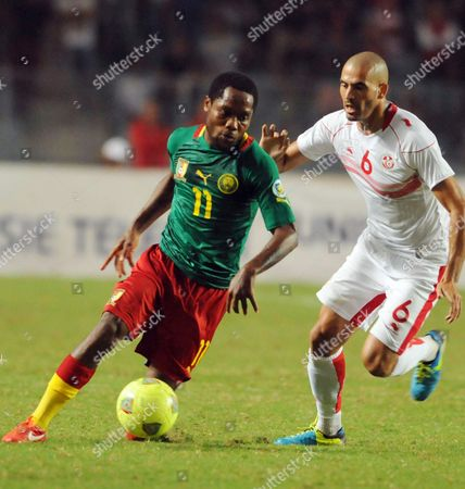 Jean Makoun, Houcin Reguid Cameroon's Jean Makoun, left, and Tunisia's Houcin Reguid vie for the ball during their round 3, first leg World Cup qualifying soccer match in Tunis, Tunisia, . The match ended 0-0