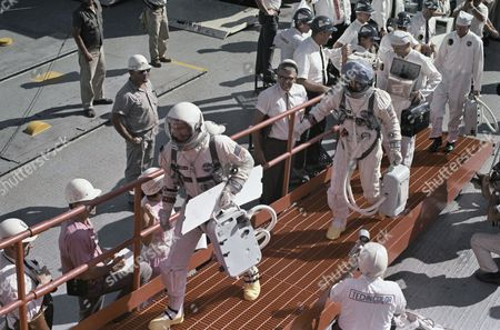 Astronauts James A. Lovell Jr and Edwin E. Aldrin Jr in space suits walking towards the launch pad, shown in an undated photo