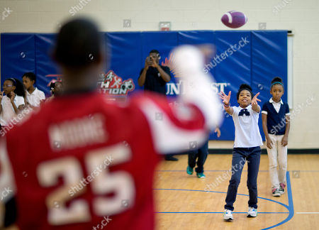 """William Moore, Tykeria Redding Atlanta Falcons' William Moore, left, throws a pass to M. Agnes Jones Elementary School fifth grader Tykeria Redding as the NFL football team takes part in the volunteer project, """"Hometown Huddle"""", in Atlanta. Team members visited six metro Atlanta schools promoting physical fitness and delivering new sports equipment in addition to serving lunch to the homeless at other area locations"""