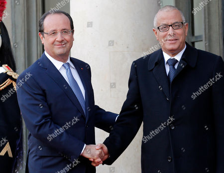 Libyan Prime Minister Ali Zeidan, right, is greeted by French President Francois Hollande at the Elysee Palace, in Paris, . France is hosting dozens of African leaders for a summit on security, just as the French military is launching an intervention in the Central African Republic and encouraging African governments to take more responsibility for peacemaking on the continent