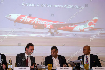 From left, Fabrice Bregier, President and CEO of Airbus, Air Asia Group cofounder and director Tony Fernandes and Air Asia CEO Azran Osman-Rani exchnage documents during a press conference announcing the signature of a firm order of 25 more A330-300 with Airbus in Paris, . Airbus has made several big deals with Asian airlines, and its parent company is putting its emphasis on civil aviation as part of a new restructuring aimed at becoming more profitable