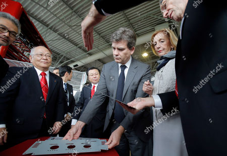 Mitsuo Okamoto, President and CEO of Amada, a Japanese manufacturer of metal processing equipment & machinery, second left, French Minister for Industrial Recovery Arnaud Montebourg, center, and French Minister for Foreign Trade Nicole Bricq listen to explanations as they visit the Amada's French subsidiary company in Tremblay en France, outside Paris, . The company manufactures metal cutting, forming, shearing, and punching machines