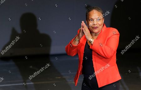 French Justice Minister Christine Taubira waves on stage during a gala ceremony against racism, in Paris, . The French government has opened a racism investigation after a far-right magazine cover compared the country's black justice minister to a monkey
