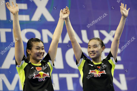 China's Bao Yixin, right, and Tang Jinhua celebrate on the podium after defeating China's Qing Tian and Zhao Yunlei during their women's doubles final match of the French Open badminton tournament in Paris