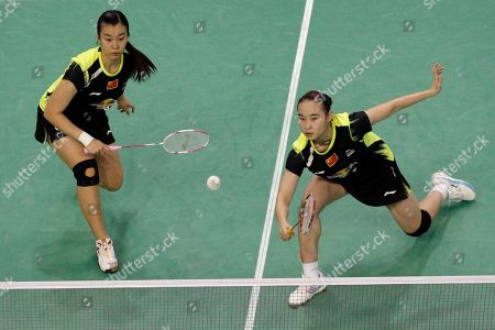 China's Bao Yixin, right, and Tang Jinhua play a shot against China's Qing Tian and Zhao Yunlei during their women's doubles final match of the French Open badminton tournament in Paris