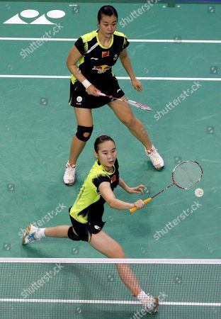 China's Bao Yixin, bottom, and Tang Jinhua play a shot against China's Qing Tian and Zhao Yunlei during their women's doubles final match of the French Open badminton tournament in Paris