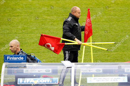 Finland's soccer head coach Mixu Paatelainen carries flags during a training session at the Stade de France stadium in Saint Denis, north of Paris, ahead of their 2014 World Cup Group I qualifying soccer match against France