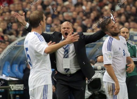 Finish head coach Mixu Paatelainen, second right, reacts as he watches his players, Veli Lampi, left, and Perparim Hetemaj during their group I World Cup qualifying soccer match between France and Finland, at the Stade de France stadium in Saint Denis, outside Paris