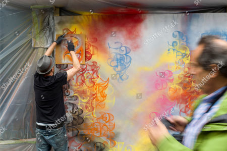 British artist Nick Walker, left, draws a painting in the street outside Drouot auction house, in Paris, . This painting is one among dozens of art pieces from street artists which will be auctioned Friday Oct. 25