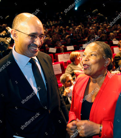 French Justice Minister Christine Taubira, right, and Secretary General of France's Socialist Party, Harlem Desir talk during a gala ceremony against racism, in Paris, . The French government has opened a racism investigation after a far-right magazine cover compared the country's black justice minister to a monkey