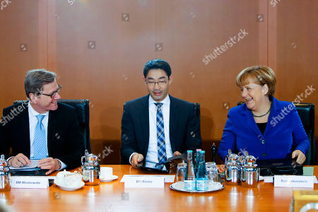 German Chancellor Angela Merkel, right, chairwoman of the Christian Democratic Union party talks to outgoing Foreign Minister Guido Westerwelle and Economic Minister and Vice Chancellor Philipp Roesler of the Free Democrats during a cabinet meeting in Berlin